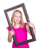 Girl holding frame around face Royalty Free Stock Image