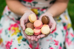 Girl holding French macaroons in hands Stock Photos