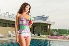 Girl holding fresh cocktail drink. Beautiful young sexy girl standing on pool side holding fresh cocktail drink Stock Photo