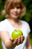 Girl holding a fresh green apple. Girl holding a beautiful, fresh green apple outdoors on a summer day Royalty Free Stock Photo