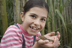 Girl Holding Frog Outdoors Stock Photo