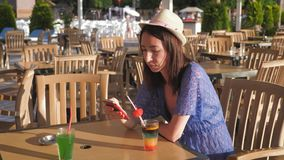 Girl holding a fruit cocktail sitting in a tropical cafe near the beach. The concept of a summer holiday on the beach. stock footage