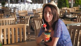 Girl holding a fruit cocktail sitting in a tropical cafe near the beach. The concept of a summer holiday on the beach. Girl holding a fruit cocktail sitting in stock video footage