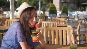 Girl holding a fruit cocktail sitting in a tropical cafe near the beach. The concept of a summer holiday on the beach. Girl holding a fruit cocktail sitting in stock footage