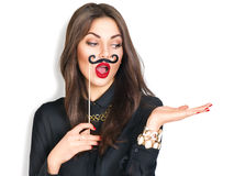 Girl holding funny mustache on stick and showing empty copyspace Royalty Free Stock Image