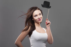 Girl holding funny paper cylinder hat on stick, isolated, gray background. Joyful young fashion woman smile, hair motion Royalty Free Stock Images