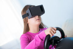 Girl holding a gaming computer wheel getting experience using VR-headset glasses Royalty Free Stock Image