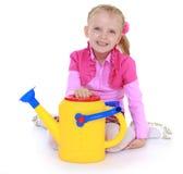 Girl holding a garden watering can. Royalty Free Stock Photos