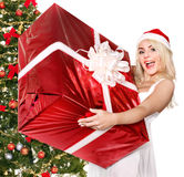 Girl holding gift box by christmas tree. Stock Images