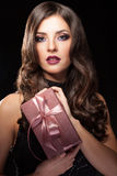 Girl holding gift box in hands on black background Royalty Free Stock Images