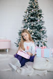 Girl holding a gift box near the Christmas tree. Kid opening Xmas present Stock Photography