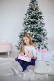 Girl holding a gift box near the Christmas tree. Kid opening Xmas present Stock Photo