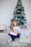 Girl holding a gift box near the Christmas tree. Kid opening Xmas present Stock Photos
