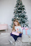 Girl holding a gift box near the Christmas tree. Kid opening Xmas present Stock Images