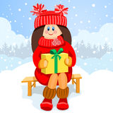 Girl holding a gift box and smiling. Stock Image