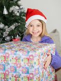 Girl Holding Gift By Christmas Tree Stock Photo