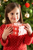 Girl Holding Gift In Front Of Christmas Tree Stock Photos