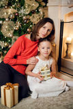Girl holding gifts and mother sitting near christmas tree stock photo