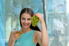 Girl holding a glass full of white wine in her right hand Royalty Free Stock Photos