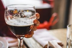 Girl holding a glass half filled with dark beer. royalty free stock images