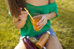 Girl holding a glass of juice in her hands. On the grass Stock Images