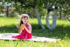 The girl is holding a glass with juice in her hands. royalty free stock photo