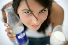 Girl holding glass of milk and bottle Stock Photo