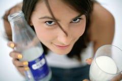 Girl holding glass of milk and bottle Stock Photo