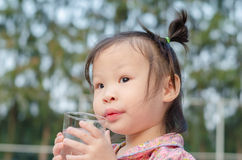 Girl holding a glass of water Stock Photography