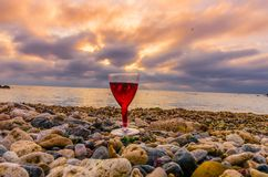 Girl holding a glass with wine during the sunset. On the sea. Photo taken in the summer season in Odesa city stock photography
