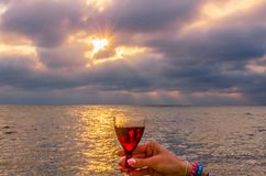 Girl holding a glass with wine during the sunset. On the sea. Photo taken in the summer season in Odesa city royalty free stock images