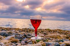 Girl holding a glass with wine during the sunset. On the sea. Photo taken in the summer season in Odesa city stock photo
