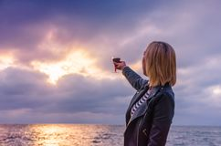Girl holding a glass with wine during the sunset. On the sea. Photo taken in the summer season in Odesa city stock images