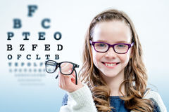 Girl holding glasses with test chart in background. Royalty Free Stock Photos