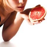 Girl holding grapefruit half Royalty Free Stock Image