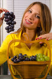 Girl holding grapes Stock Photos