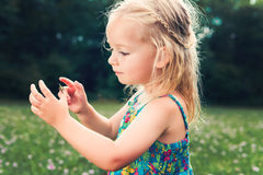 Girl holding grasshopper, curiosity and education concept. Adorable young girl holding grasshopper, curiosity and education concept royalty free stock image