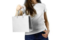 Girl holding a gray paper gift bag. Close up. Isolated background stock images