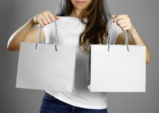 Girl holding a gray paper gift bag. Close up. Isolated background stock photography
