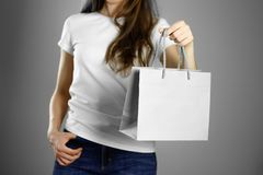 Girl holding a gray paper gift bag. Close up. Isolated background stock photo