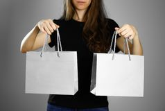 Girl holding a gray paper gift bag. Close up. Isolated background royalty free stock images