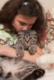 Girl holding gray tabby cat Royalty Free Stock Images