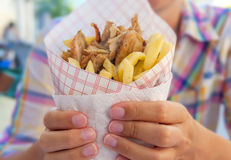 Girl holding Greek gyro with fries close up on table. Close Royalty Free Stock Photography