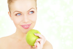 Girl holding a green apple Stock Photos