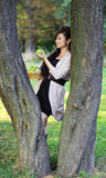 Girl holding a green apple leaning on a tree Stock Photography