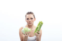 Girl holding a green cabbage and celery Royalty Free Stock Photography