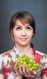 The  girl is holding the green grape Stock Photography