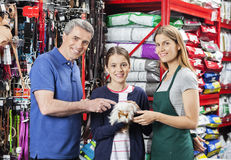 Girl Holding Guinea Pig With Father And Saleswoman In Store. Portrait of happy girl holding guinea pig while standing with father and saleswoman in pet store Royalty Free Stock Photography