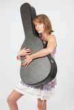 Girl holding guitar case Stock Images
