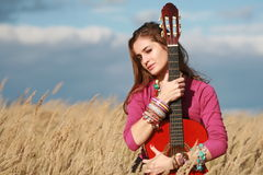 Girl holding a guitar in field Stock Images